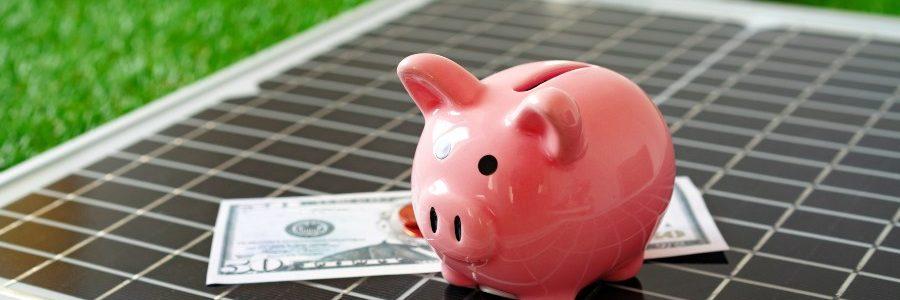 Solar panel model and piggy bank close up, energy savings concept